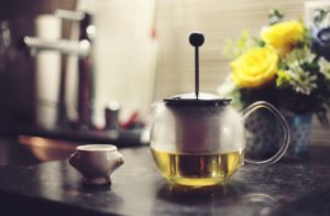 An infuser with green tea and a tea cup prepared for degustation.