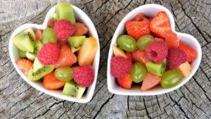 Two bowls full of various fresh fruit.